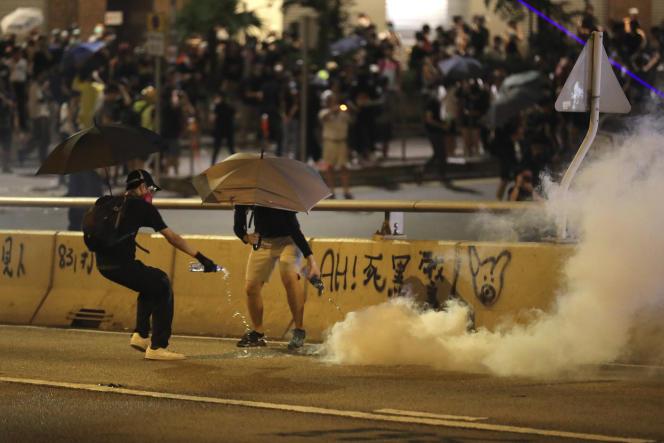 Des manifestants prodémocratie tentent de noyer une grenade de gaz lacrymogène, samedi 28 septembre.
