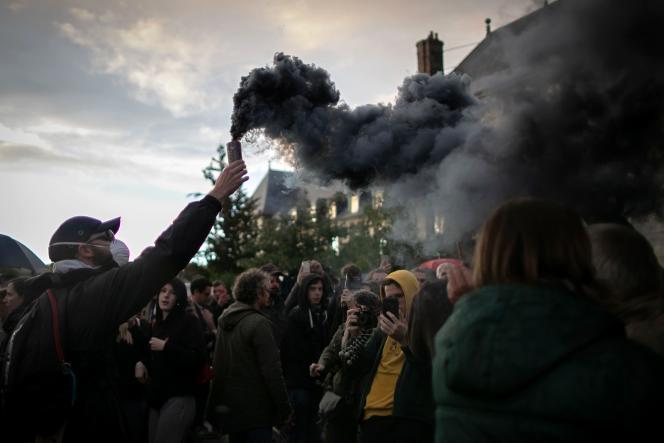 Un manifestant brandit un fumigène à Rouen, mardi 1er octobre.