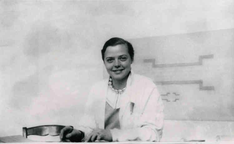 Charlotte Perriand a 26 ans et rejoint l'atelier du Corbusier et Pierre Jeanneret après s'être fait remarquer grâce à son «Bar sous le toit» exposé au Salon d'automne deux ans auparavant. Avec son fameux collier «roulement à bille» qu'elle a fabriqué, elle pose devant sa planche à dessin dans l'atelier de la rue de Sèvres.