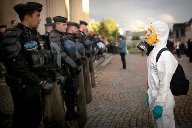 Une personne en combinaison face à des policiers lors d'une manifestation visant à demander plus de transparence, le 1er octobre.