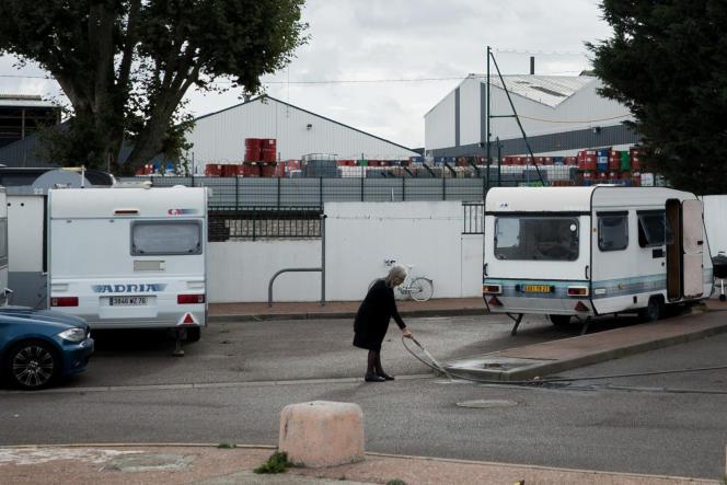 L'aire des gens du voyage au Petit-Quevilly est située à 500mètres de l'usine Lubrizol. Une femme nettoie au jet son emplacement. Derrière la caravane, on peut distinguer les bidons d'une autre usine de lubrifiant, Total.