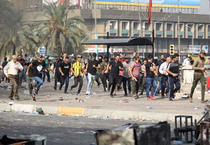 Des manifestants fuient la police antiémeute, à Bagdad, le 3 octobre.
