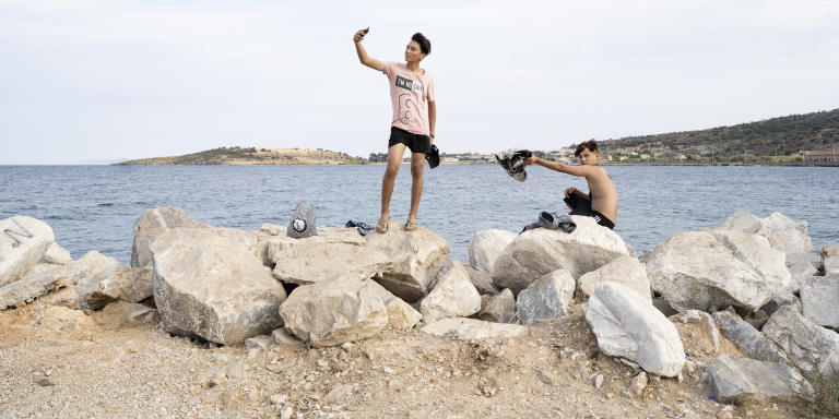 Des jeunes viennent s'amuser et prennent la pose le temps d'une photo dans la zone portuaire de Moria, sur l'île de Lesbos. Le 19 septembre.
