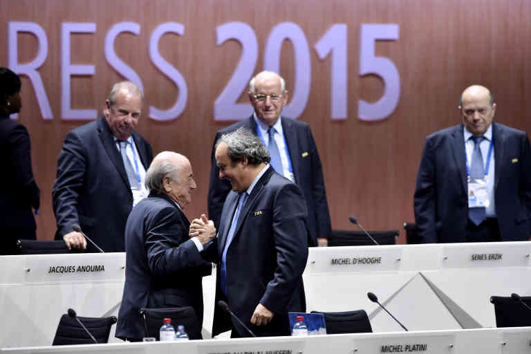 FIFA President Sepp Blatter (Foreground-L) shakes hands with UEFA president Michel Platini after being re-elected following a vote to decide on the FIFA presidency in Zurich on May 29, 2015.   Sepp Blatter won the FIFA presidency for a fifth time after his challenger Prince Ali bin al Hussein withdrew just before a scheduled second round.    AFP PHOTO /  MICHAEL BUHOLZER (Photo by MICHAEL BUHOLZER / AFP)