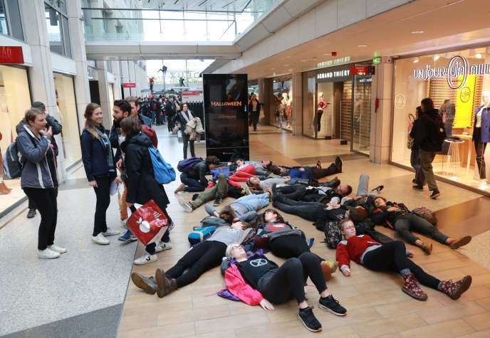Des manifestants s'allongent lors d'une manifestation, le 5 octobre 2019, dans le centre commercial Italie 2, à Paris, appelé par le mouvement écologiste Extinction Rébellion, qui a annoncé la perturbation de 60 villes à travers le monde à partir du7octobre pour une quinzaine de jours de désobéissance civile, mettant en garde contre une «apocalypse» de l'environnement.