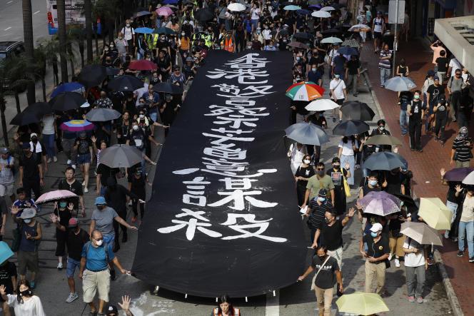 Des manifestants sous une bannière déclarant:« La police tue volontairement».