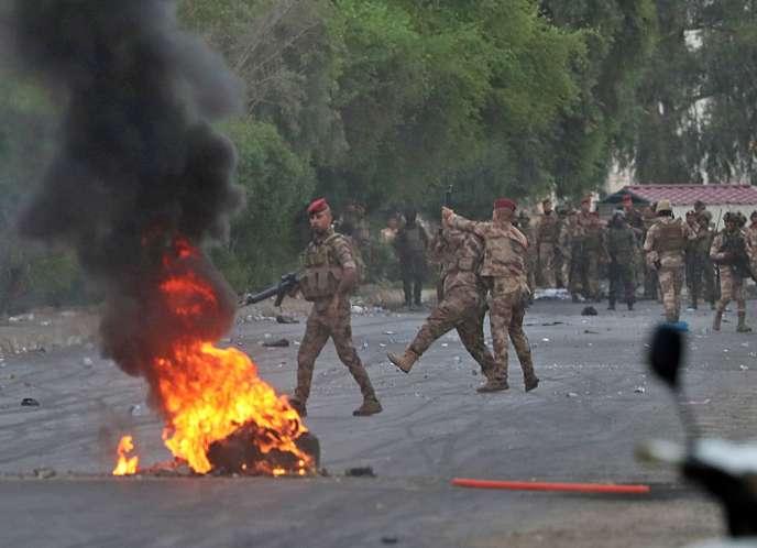 Des soldats irakiens face à des manifestants, le 6 octobre à Bagdad.