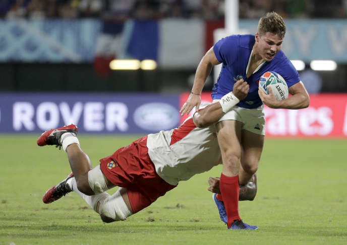 Rugby La défense tongienne tentant de transformer le col rond du maillot français en col en V.