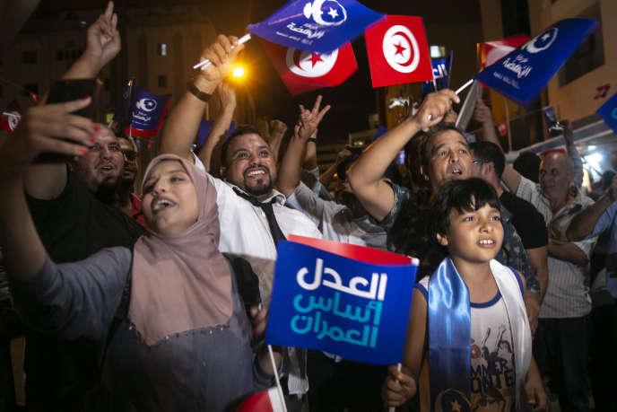 Des Tunisiens manifestent leur joie, à Tunis, après l'annonce des premiers résultats des législatives donnant le parti islamo-conservateur Ennahda en tête, dimanche 6 octobre.