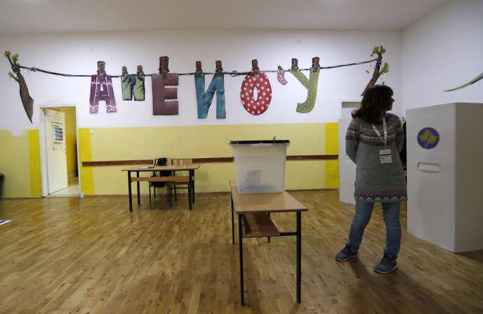 Une membre de la commission électorale au Kosovo attend les premiers votants lors des élections du dimanche6 octobre.