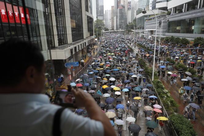 Un homme prend en photo les manifestants portant des masques et tenant des parapluies en signe de protestation, dimanche 6 octobre à Hongkong.