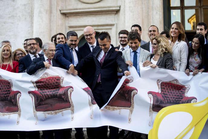 Le ministre des affaires étrangères italien, Luigi di Maio, déchire une banderole représentant des fauteuils vides symbolisant le nombre excessif de parlementaires, le 8 octobre, à Rome.