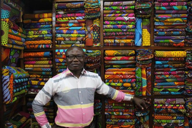 Albert, début octobre 2019, dans sa boutique du marché de Makola, à Accra, la capitale du Ghana, vend vêtements et coupons de tissus« Made in Ghana».