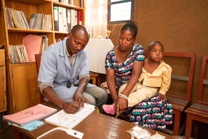 Em Musanze, Ruanda, um agente comunitário de saúde examina uma criança suspeita de malária em 2019.