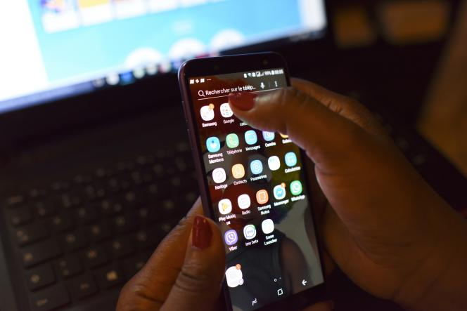 A woman uses a smartphone in front of a laptop on April 3, 2019, in Abidjan. - According to the figures of the platform of the fight against cybercrime (PLCC) of the national police, nearly one hundred crooks of the internet, were arrested in 2018 in Ivory Coast, a country known for its scammers on the web, has announced on April 2, 2019 the Ivorian authority of regulation of the telephony. (Photo by ISSOUF SANOGO / AFP)