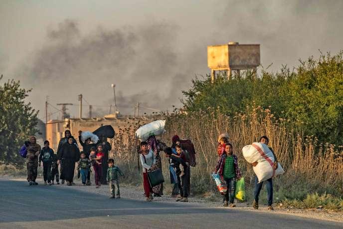 Des civils fuient Ras Al-Aïn, ville syrienne proche de la frontière turque, le 9 octobre.