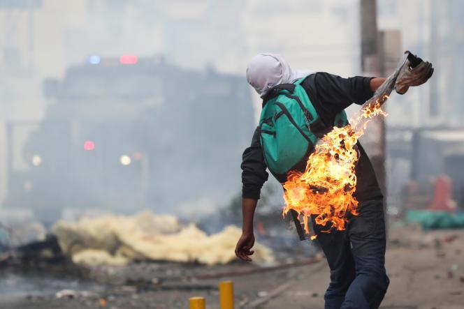 Un manifestant en train de lancer un projectile enflammé, à Quito, vendredi 11 octobre.