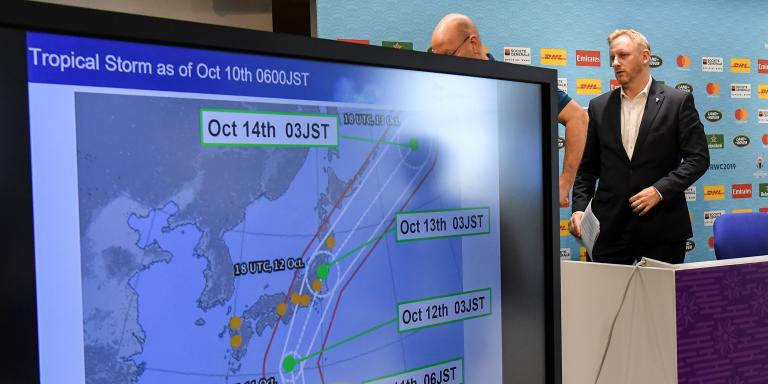 Tournament director of the Japan 2019 Rugby World Cup Alan Gilpin (R) walks past a screen showing the path of the approaching typhoon Hagibis, which will affect upcoming World Cup matches, in Tokyo on October 10, 2019. Rugby World Cup organisers took the unprecedented step of cancelling games -- England v France, and New Zealand v Italy -- on October 10 as Super Typhoon Hagibis bears down on Japan. / AFP / William WEST