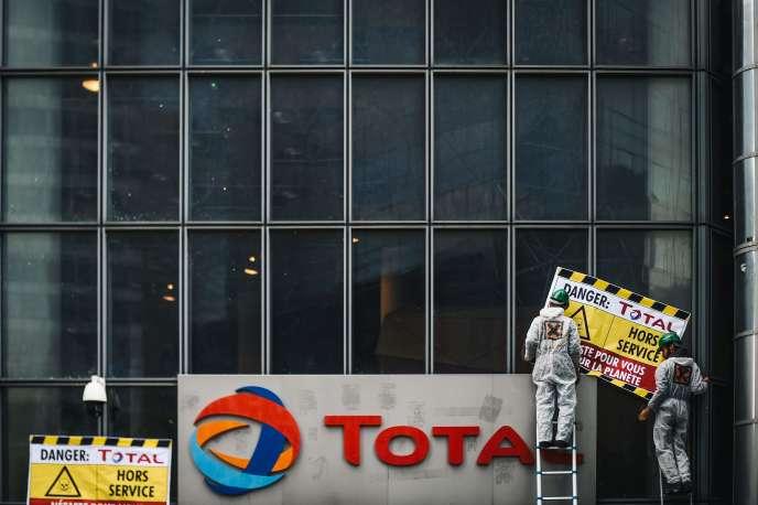 Des militants posent des pancartes devant le siège de Total à La Défense, samedi 12 octobre.