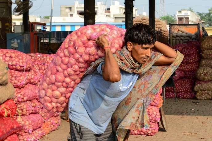 Dans un marché, à la périphérie d'Amritsar, le 19 septembre, un homme porte un sac d'oignons, aliment de base, omniprésent dans la cuisine indienne.
