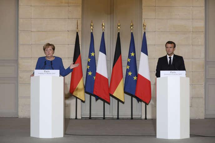 Le président français Emmanuel Macron et la chancelière allemande Angela Merkel donnent une conférence de presse au Palais de l'Elysée à Paris, dimanche 13 octobre 2019