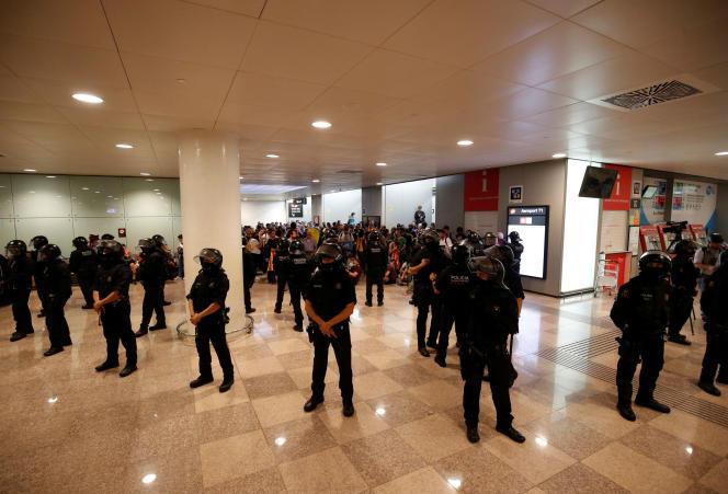 Forces de l'ordre et manifestants indépendantistes devant l'accès à la station de métro de l'aéroport El Prat de Barcelone, le 14 octobre.