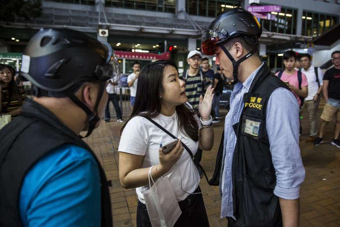 Un policier échange avec une femme après des affrontements avec des manifestants antigouvernementaux à Hongkong, le 22septembre2019.