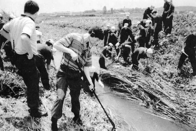 Des enquêteurs examinent la scène de crime après le meurtre de 9 femmes àHwaseong, Corée du Sud, en juillet 1993.