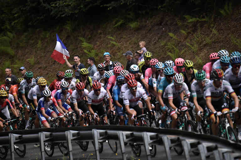 The pack rides in a curve during the sixth stage of the 106th edition of the Tour de France cycling race between Mulhouse and La Planche des Belles Filles, on July 11, 2019. (Photo by Marco Bertorello / AFP)