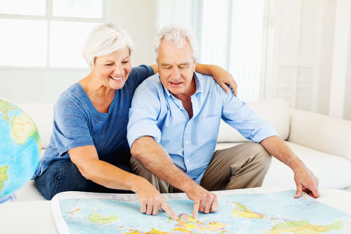 Senior couple choosing travel destination on map at home. Horizontal shot.