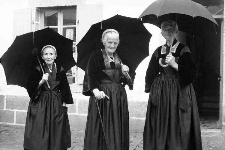 «Au détour d'une rue, je croise ces trois Bretonnes qui discutaient. Voyant que je sortais mon appareil, elles m'ont fait face avec amusement et plaisir. Elle ne se doute pas que les parapluies les encadrent si joliment. C'est une photographie que j'affectionne particulièrement et qui dépasse, pour moi, l'anecdote. »