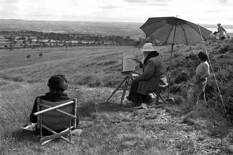 «J'ai redécouvert cette photographie à l'occasion de ce travail de recherche sur la Bretagne des années 1950. Retrouverait-on encore aujourd'hui une telle scène ? Le peintre installé avec son chevalet, son parasol et sa femme qui attend patiemment le chef-d'œuvre achevé».