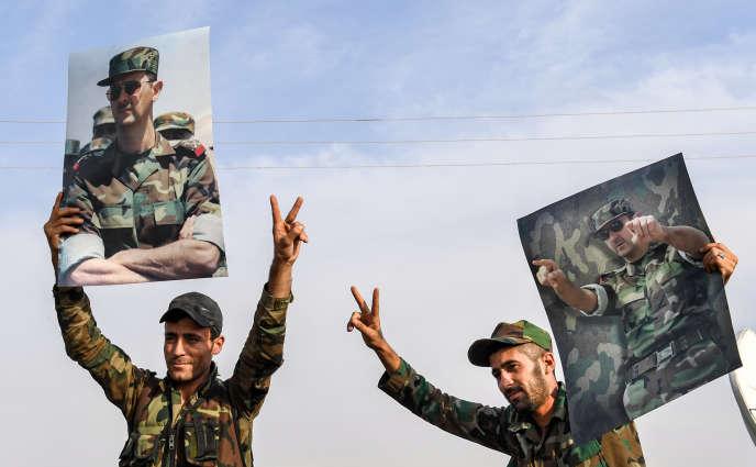 Des soldats syriens brandissent le portrait du président Bachar Al-Assad après s'être déployés dans la ville de Manbij, le 15 octobre.