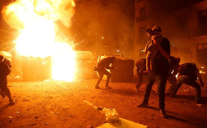 Des manifestants, derrière une barricade en feu, dans les rues de Barcelone, le 18octobre.