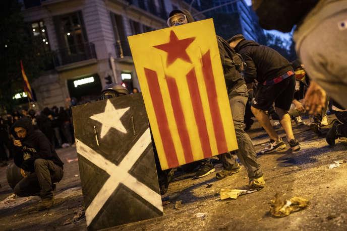 Des manifestants équipés de boucliers avec le drapeau indépendantiste catalan affrontentla police à Barcelone, le 18 octobre.