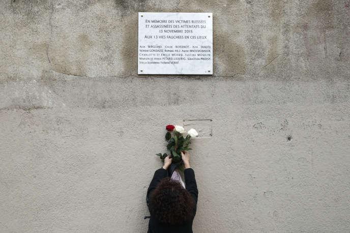 Une femme installe des fleurs en-dessous d'une plaque commémorative, près du Carillon et du Petit Cambodge, à Paris , le 13 novembre 2018.