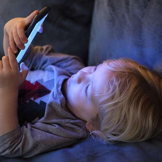 Un enfant regardant un smartphone.
