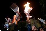 Des partisans du candidat Carlos Mesa brûlent des prospectus électoraux à La Paz, lundi 21 octobre au soir.