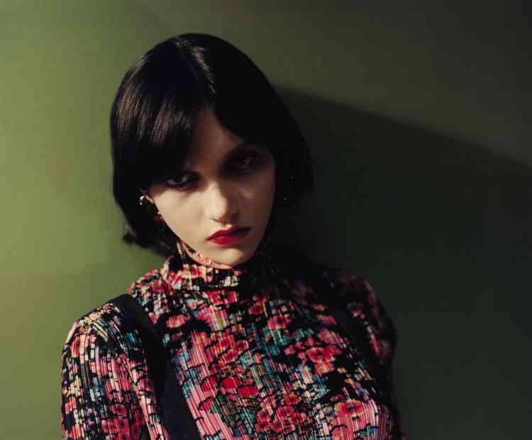 Robe plissée à imprimé floral en polyester, Givenchy.Bretelles en soie, Charvet. Créoles à anneaux multiples en or, The Attico × Alican Icoz.