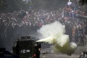 Un véhicule des forces de l'ordre face à des manifestants, à Santiago, mardi 22 octobre 2019.