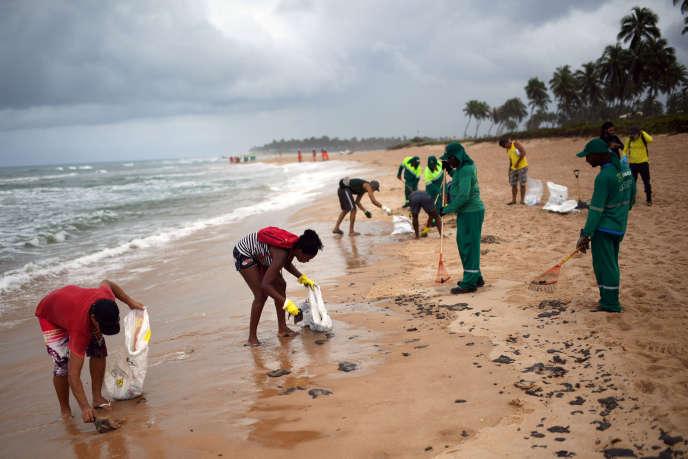 Des employés municipaux nettoient les résidus de pétrole sur la plage Barra de Jacuipe à Camacari, dans l'Etat de Bahia, le 22 octobre.