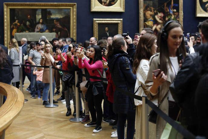 Des visiteurs photographient « La Joconde », le chef-d'œuvre de Léonard de Vinci, au musée du Louvre à Paris, le 23 octobre.