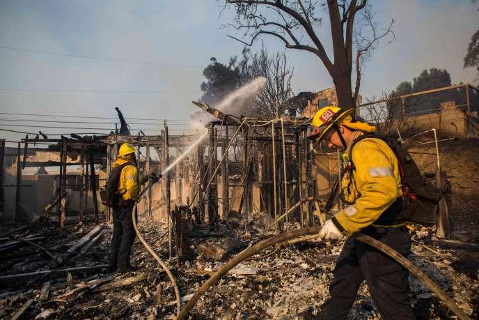 Les pompiers éteignent les dernières flammes de ce qui fut une maison, à Brentwood, lundi 28octobre.