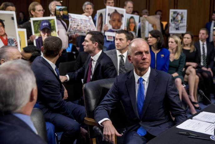 L'assistance brandit les portraits des victimes des crashs aérienspendant l'audition de Dennis Muilenburg devant le Congrès américain, le 29 octobre.