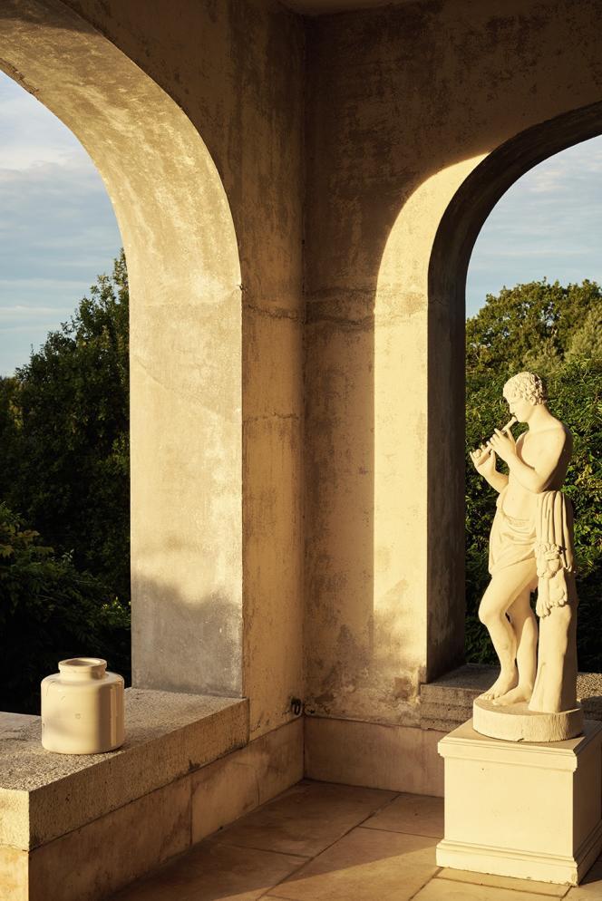 Sous la véranda, un joueur de flûte en pierre.