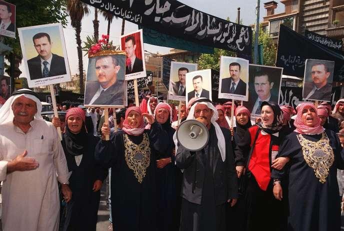 Des paysans syriens de la province de Daraa, à une centaine de kilomètres au sud de Damas, manifestent dans la capitale syrienne, le 9 juillet 2000, pour soutenir le président en exercice, Bachar Al-Assad, un jour avant le plébiscite présidentiel.