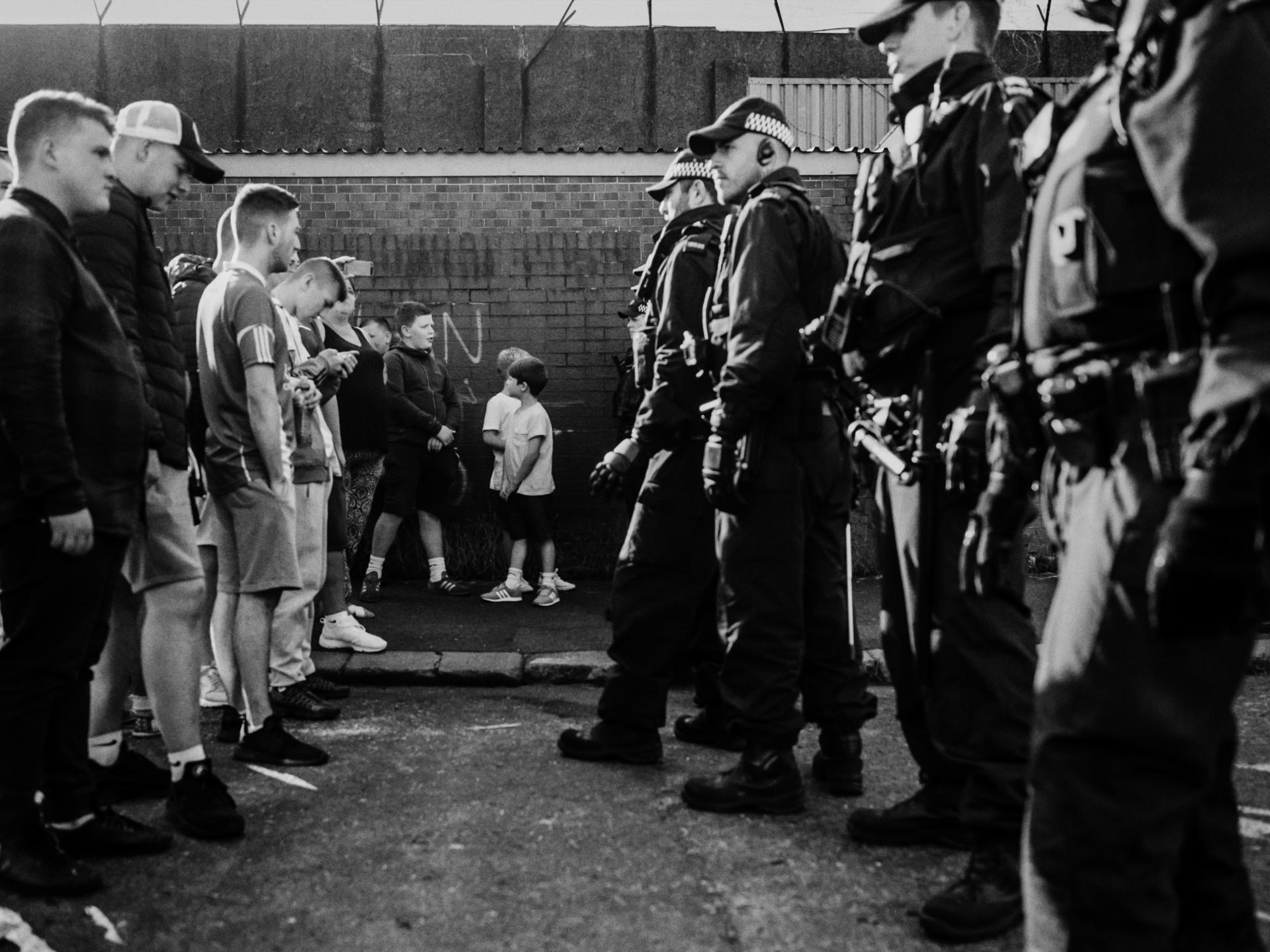Un groupe d'adolescents fait face aux policiers sur Trinity Street, dans le quartier de Carrick Hill, à Belfast.