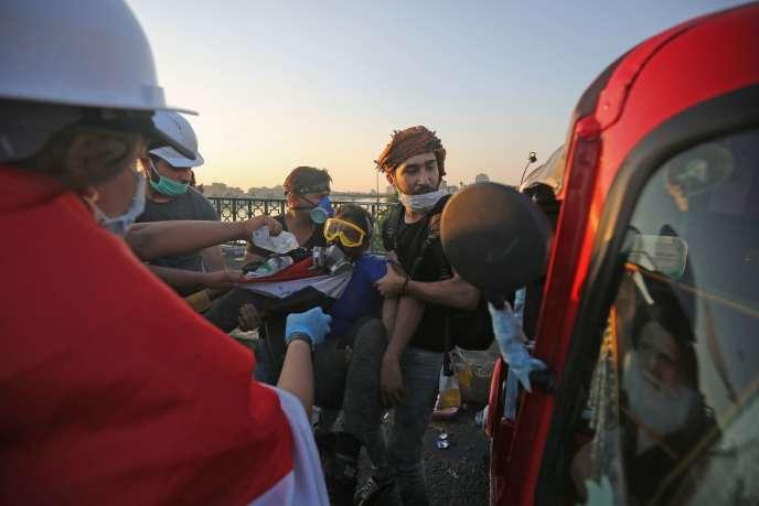 Des manifestants aident un camarade blessé près du pont Al-Sinak, à Bagdad, le 1er novembre.