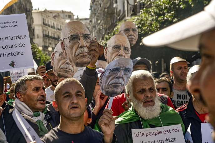 A Alger, le 1er novembre, des manifestants agitent des masques où est imprimé le visage de Lakhdar Bouregaa, un vétéran arrêté àl'été.