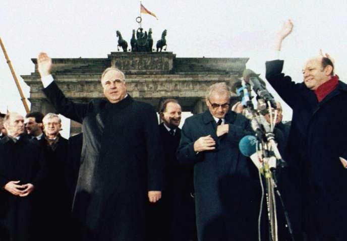 Le 22 décembre 1989, dans la photo d'archives, le chancelier ouest-allemand Helmut Kohl, à gauche, fait un signe de la main aux côtés du Premier ministre de l'Allemagne de l'Est, Hans Modrow, à droite, devant la porte de Brandebourg lors de la cérémonie d'ouverture du Mur de Berlin, 22 décembre 1989. La chute brutale du mur en 1989 et la vitesse fulgurante de la réunification ont surpris tout le monde à l'époque et ont bouleversé le système pour 16 millions d'Allemands de l'Est.